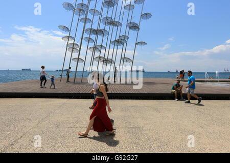 Die Menschen gehen vorbei an Georgios Zongolopoulos Schirme an der Küste der nördlichen griechischen Stadt Thessaloniki. - Stockfoto