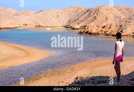 Eine touristische Dame suchen an einem malerischen Fjord - wie bei Ebbe in Bandar Khayran, Sultanat Oman - Stockfoto