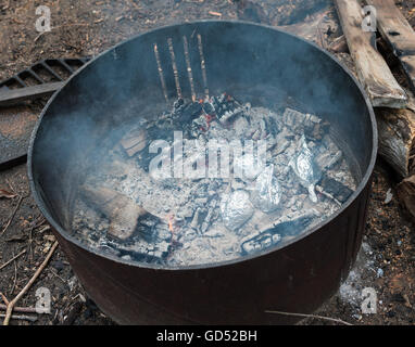 Kartoffeln in Folie Kochen auf heißen Kohlen im Feuer gewickelt - Stockfoto