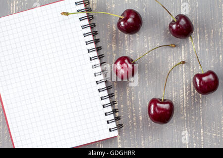 Frische Kirschen und leeren Notebook für die Aufzeichnung auf dem grauen Hintergrund Holz - Stockfoto