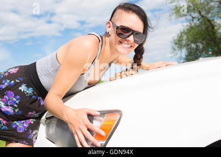 Fröhliche junge Fahrerin umarmt ihr neues Auto - Stockfoto