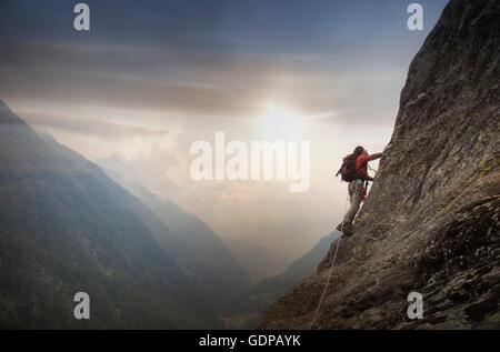 Bergsteiger auf einer Felswand über einem Tal, Alpen, Kanton Bern, Schweiz - Stockfoto