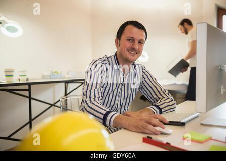Architekten arbeiten am Computer und lächelnd in Büro, Bayern, Deutschland - Stockfoto