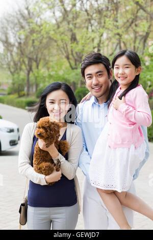 Glückliche junge chinesische Familie mit ihrem Hund - Stockfoto