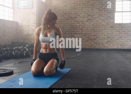 Schuss von Fitness-Frau sitzen auf Gymnastikmatte und betrachten ihre Trizeps. Muskulöse Frau, trainieren Sie im - Stockfoto