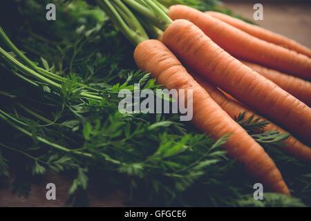 Karotten mit Grün auf Holz rustikal. - Stockfoto