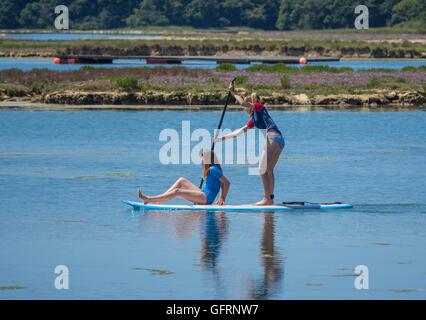 Zwei Mädchen genießen aufstehen Paddle boarding in Newtown Fluß auf der Isle Of Wight, UK - Stockfoto