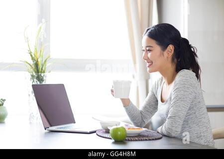 Junge Chinesin mit Laptop beim Frühstück - Stockfoto