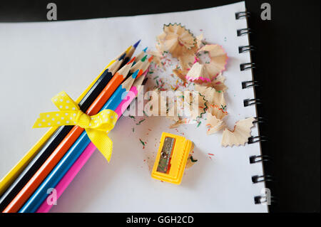 Bündel Buntstifte geschärft mit einer gelben Schleife, Spitzer und Späne - Stockfoto