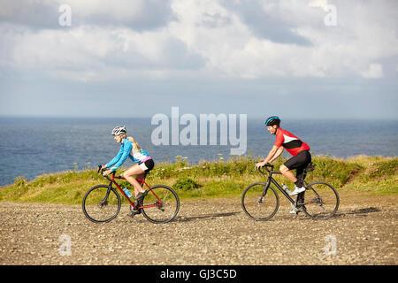 Radfahrer fahren auf Schotterstraße mit Blick auf Meer - Stockfoto