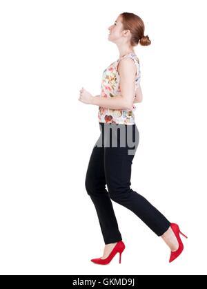 Business-Frau läuft. hinten Sie Ansicht von. gehen junges Mädchen im Anzug. Re - Stockfoto