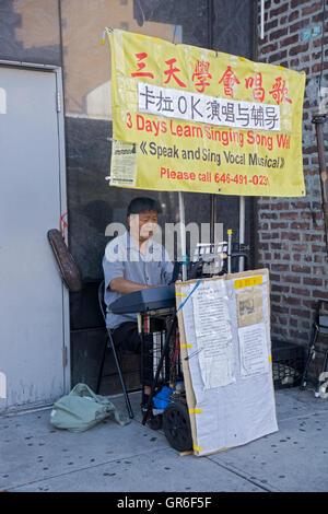Ein koreanischer Mann das Klavierspiel an der Main Street in Flushing Werbung Gesangsunterricht - Stockfoto