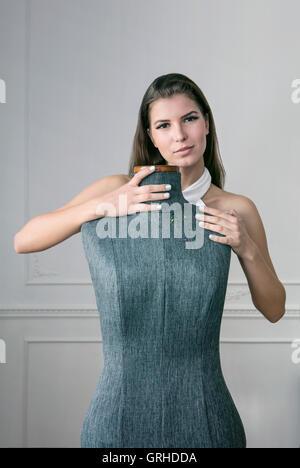 Eine junge schöne Frau arbeitet an einem Dummy Schneider als Schneiderin - Stockfoto