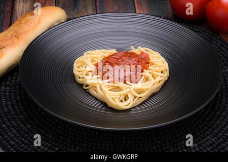 Ich liebe Nudeln, Spaghetti-Herz mit Marinara auf einer schwarzen Schale - Stockfoto