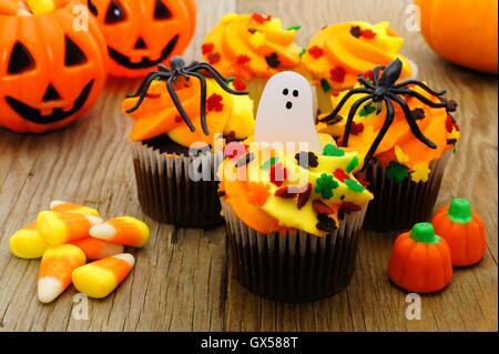 Halloween Cupcakes und Süßigkeiten auf rustikalen Holztisch - Stockfoto
