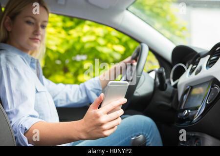Frau im Auto SMS auf Handy während der Fahrt - Stockfoto