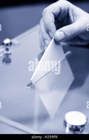 Bild einer Wahlurne und Hand setzen einen leere Stimmzettel innen, Wahlen, Abstimmungen Konzept, blau getönt - Stockfoto