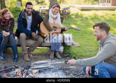 Freunde, Gitarre zu spielen und Kochen Fisch im Grill-Korb über Lagerfeuer - Stockfoto