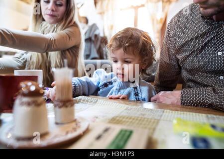 Junge Eltern mit Sohn im Restaurant Mahlzeit warten. - Stockfoto