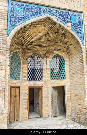 Die Ausfahrt aus dem Hof der Modari Khan Madrassah, dekoriert mit traditionellen blauen Kacheln, Buchara, Usbekistan. - Stockfoto