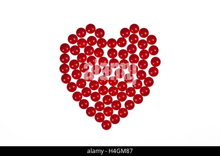Herzform aus roten Tabletten auf einem weißen Hintergrund symbolisiert Herz Medikamente oder Romantik und Valentinstag - Stockfoto