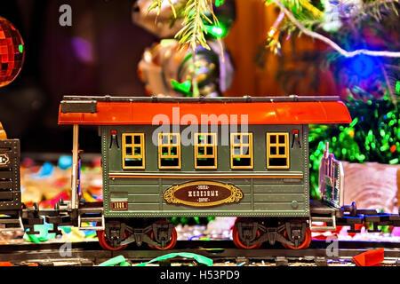 Weihnachten Spielzeug-Eisenbahn in der Nähe von einem Weihnachtsbaum mit Lichtern. - Stockfoto