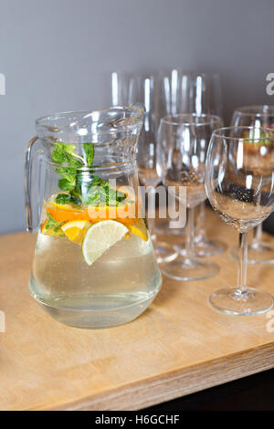 Eine Karaffe mit fruchtigen Getränk mit Minze und Zitrone und Holztablett Vorspeisen bei einem Bankett auf einem - Stockfoto