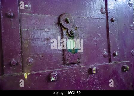 Guckloch auf eine lila Gefängnis Zellentür - Stockfoto