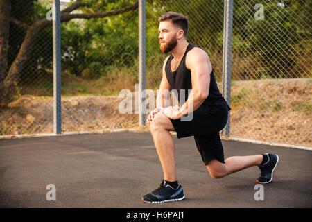 Hübscher Junge bärtige Sportler dehnen Beine beim Training im freien - Stockfoto