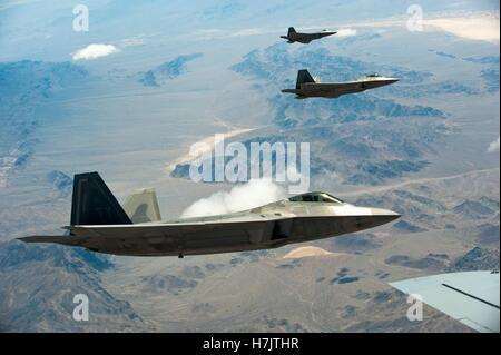 F-22 Raptor Stealth-Kampfflugzeuge fliegen über die Nevada Test und Trainingsbereich während des Trainings rote - Stockfoto