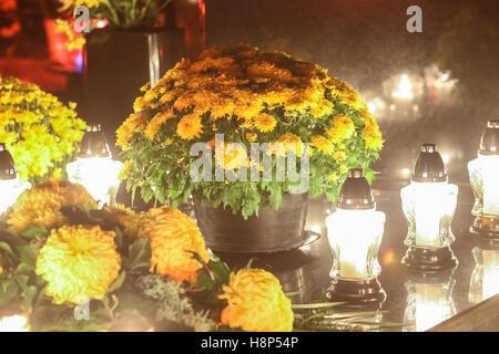 Blumenarrangements und Lampions aufgereiht auf Grabstein auf dem Friedhof an Allerheiligen in Kroatien. - Stockfoto