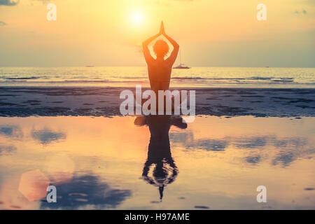 Silhouette der weiblichen Yoga am Strand nach Sonnenuntergang. - Stockfoto