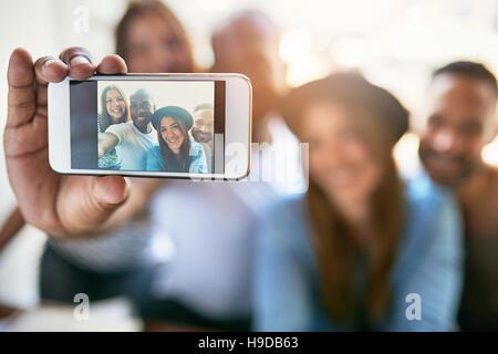 Telefon in männlicher Hand machen Selbstporträt von vier lächelnden Menschen sitzen im Lichtraum hautnah. - Stockfoto