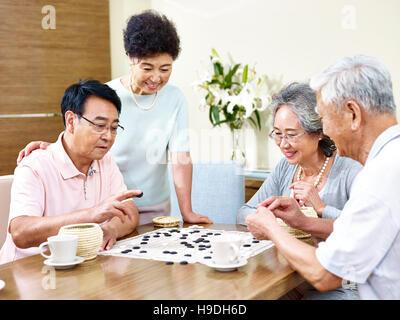 zwei ältere Männer spielen Weiqi (oder Go-Spiel) zu Hause mit ihren Frauen beobachten - Stockfoto