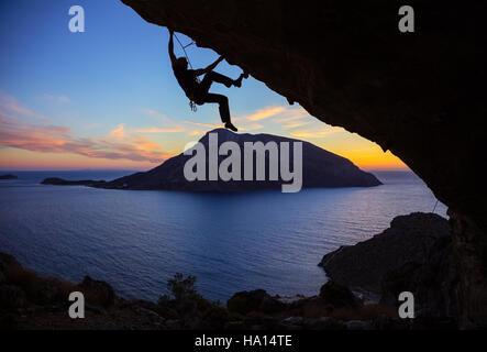 Junger Mann Klettern entlang Dach in Höhle bei Sonnenuntergang - Stockfoto