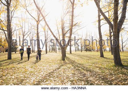 Schen Jungen zu Fuß mit Skateboards und Fahrrad im sonnigen Herbst park - Stockfoto