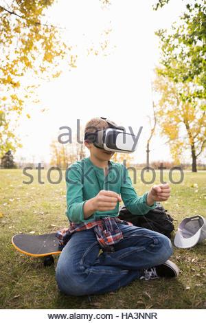 Schen jungen mit virtual-Reality-Simulator Gläser auf Skateboard im Herbst park - Stockfoto