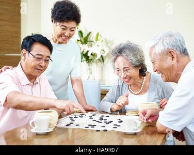 zwei hochrangige asiatische Männer spielen Weiqi (oder Go-Spiel) zu Hause mit ihren Frauen beobachten. - Stockfoto