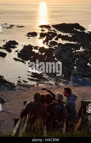 Touristen eine Selfie bei Sonnenuntergang, Rockham Bay, in der Nähe von Mortehoe, Devon. - Stockfoto