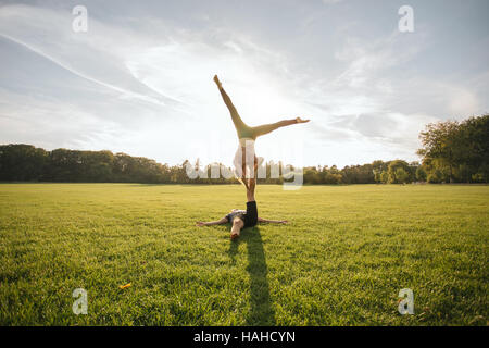 Starke junge Paar Acroyoga im Freien zu tun. Mann hält und Frau auf einem Bein balancieren. - Stockfoto