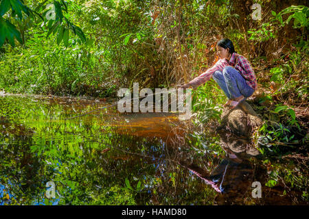 Eine junge Khmer kambodschanische Frau hockt neben einem Wald Fischen für ihre Familie in Banteay Srei, Königreich - Stockfoto