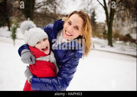 Mutter mit Tochter vor Hintergrund der schneebedeckten Stadt Hof. Die Frau und Mädchen sind in hellen warmen Down - Stockfoto