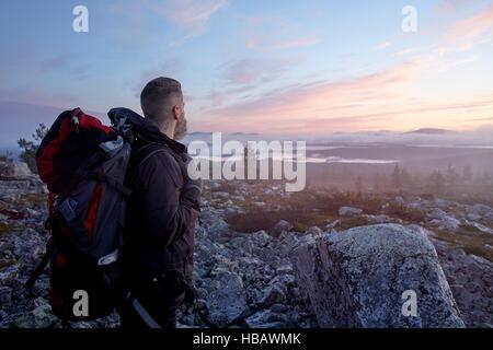 Wanderer genießen Sonnenuntergang auf Klippe oben, Sarkitunturi, Lappland, Finnland - Stockfoto