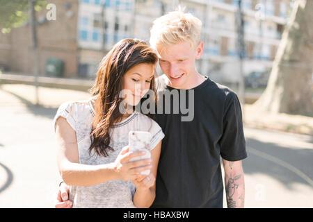 Frau und Freund lesen Smartphone aktualisieren auf Basketballplatz - Stockfoto