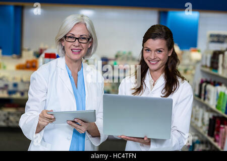 Mit digitalen Tablet und Laptop in Apotheke Apotheker - Stockfoto