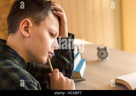 Jungen denken über ein Buch auf Schreibtisch zu Hause - Stockfoto