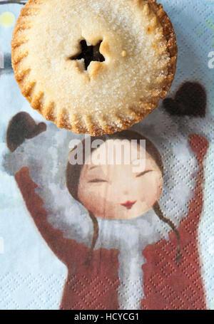 M & S Christmas, die alle Mince Pie auf Serviette mit Mädchen haltende Hand, butter - Stockfoto