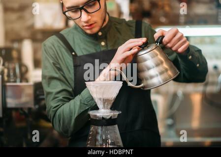 Kellner mit schwarzer Schürze und Brillen gießt heißes abgekochtes Wasser im Kaffee Topf stehen am Tresen. - Stockfoto
