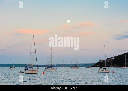 Vollmond über Yachten auf einen ruhigen türkisfarbenen Meer mit roten Zirruswolken verankert. - Stockfoto