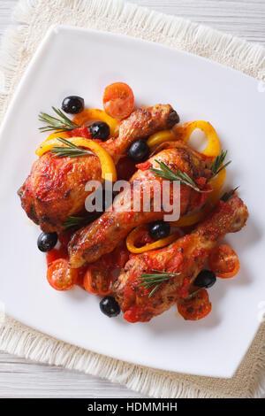 Hähnchenschenkel in Tomatensauce mit Paprika, Oliven und Rosmarin auf einem weißen Teller, vertikale Ansicht von - Stockfoto